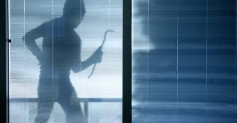 Inbreker met koevoet kijkt door raam
